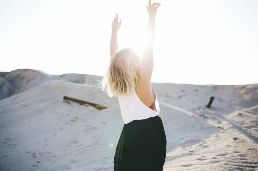 woman lifting her hands up